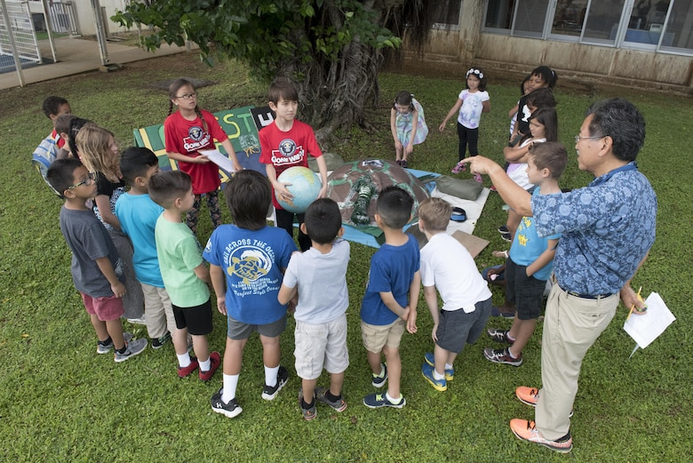 Children from Kadena Elementary School's English as a Second Language team present a life-sized replica of a giant tortoise to their classmates May 22, 2017, at Kadena Air Base, Japan.  The school's 60 ESL members worked together with parents and teachers over the course of three weeks to construct props and other stations for the event. (U.S. Air Force photo by Senior Airman John Linzmeier)