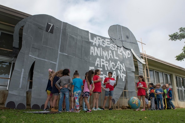 Children from Kadena Elementary School gather around a cardboard cutout of the world's largest land-walking animal, an African elephant, May 22, 2017, at Kadena Air Base, Japan. The event produced by members of the school's English as a Second Language team and was held to teach cross-curricular subjects such as science, health, history and geography. (U.S. Air Force photo by Senior Airman John Linzmeier)