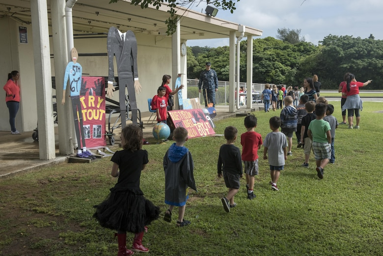 Children from Kadena Elementary School walk from one educational booth to another May 22, 2017, at Kadena Air Base, Japan. The school's English as a Second Language team presented 12 stations representing Guinness Book of World Records to the whole school. (U.S. Air Force photo by Senior Airman John Linzmeier)