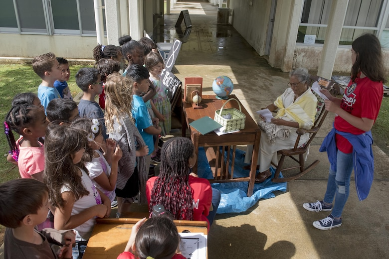 Children from Kadena Elementary School gather around Selva Jones, title?, during an interactive learning experience May 22, 2017, at Kadena Air Base, Japan. Jones portrayed the role of La Maestra Chucha, who taught school for 82 years and was acknowledged by the Guinness Book of World Record's as the world's most durable teacher. (U.S. Air Force photo by Senior Airman John Linzmeier)