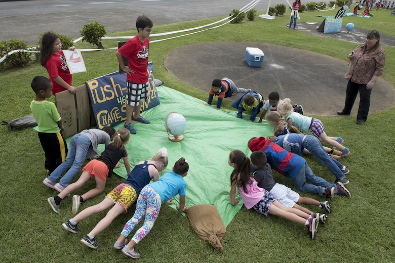 Children from Kadena Elementary School practice pushup as an educational activity May 22, 2017, at Kadena Air Base, Japan. Various educational booths were set up by the school's English as a Second Language program to demonstrate a number of world records, such as the most pushups achieved within a 24-hour period, which is 46,001. (U.S. Air Force photo by Senior Airman John Linzmeier)