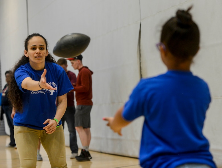 "U.S. Army Sgt. Brenda Contreras, 5th Quartermaster, 21st Special Troops Battalion, 21st Theater Sustainment Command, tosses a football to Aviella, a special Olympian, during a break on Ramstein Air Base, Germany, May 19, 2017. Aviella and the other students competing in the 2017 Spring Kaiserslautern Military Community Special Olympics received a volunteer to accompany them as a ""buddy"" throughout the day. (U.S. Air Force photo by Staff Sgt. Timothy Moore)"