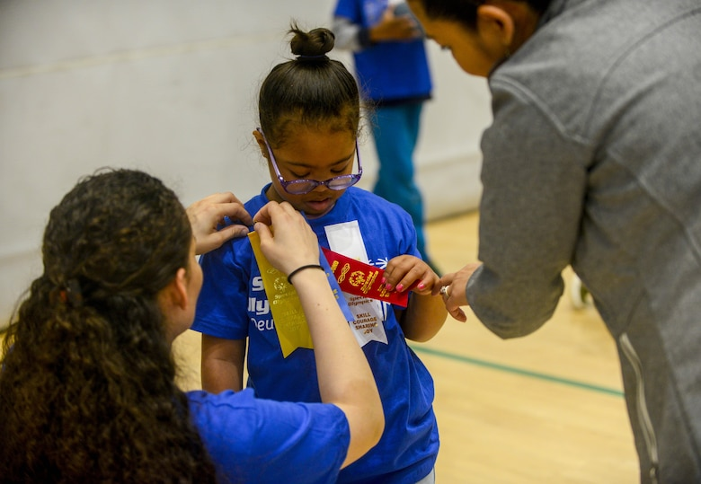"U.S. Army Sgt. Brenda Contreras, 5th Quartermaster, 21st Special Troops Battalion, 21st Theater Sustainment Command, pins a ribbon on Aviella, a special Olympian, on Ramstein Air Base, Germany, May 19, 2017. Aviella and the other students competing in the 2017 Spring Kaiserslautern Military Community Special Olympics received a volunteer to accompany them as a ""buddy"" throughout the day. (U.S. Air Force photo by Staff Sgt. Timothy Moore)"