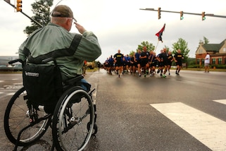 Retired paratrooper, Harry Shaw, salutes paratroopers assigned to the 82nd Airborne Division as they shout cadence while running during the All American Week division run on Longstreet Road at Fort Bragg, N.C., May 22, 2017. Army photo by Spc. Dustin D. Biven