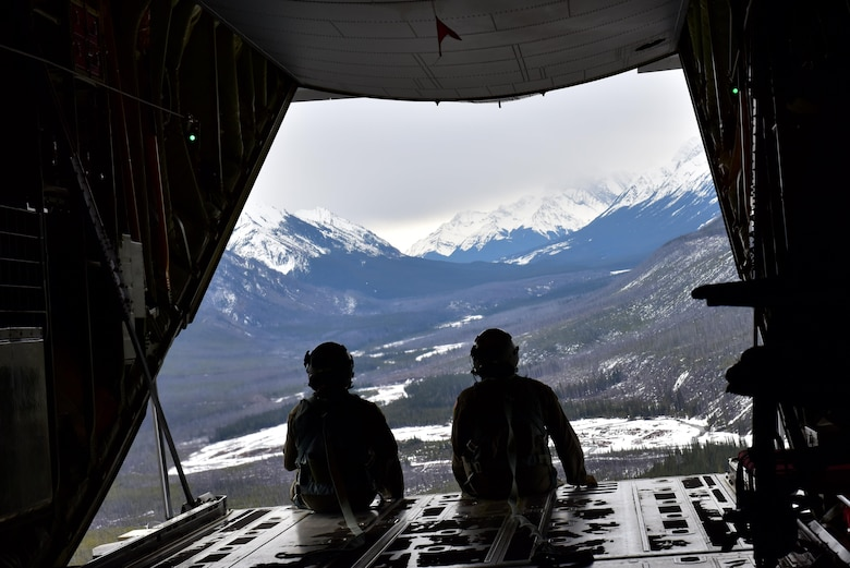 U.S. Air Force Tech. Sgt. Ryan Maxey (right) and Airman 1st Class Tyler Wilson, 41st Airlift Squadron Loadmasters, watch out of the back of their C-130J after a simulated cargo drop while navigating through the Canadian Rockies during the Fanatic Pegasus exercise with Royal Canadian air forces in Alberta, Canada, April 20, 2017. This is the first time American forces have participated in this exercise which establishes air and ground forces in unfamiliar terrain to work on communication and rapid deployment of those resources. (U.S. Air Force photo by Staff Sgt. Jeremy McGuffin)