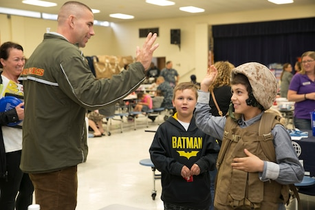 Staff Sgt. William Hobson, operations chief, G-1, U.S. Marine Corps Forces Command, high fives a student at Tarrallton Elemantary School in Norfolk, Va., after helping him put on tactical gear such as a Kevlar helmet, flak vest, and backpack, during a Military Child Appreciation event, April 24. The event was held to give the schools and communities in the city of Norfolk an opportunity to recognize the children of service members. (Official U.S. Marine Corps photo by Cpl. Logan Snyder/ Released)