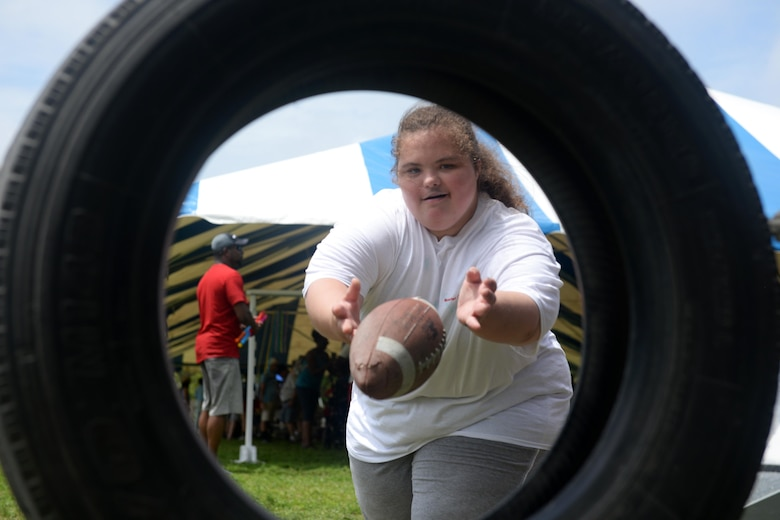 Madyson McManus, Area 3 athlete, throws a football through a tire during the Special Olympics Mississippi 2017 Summer Games at Olympic Village May 20, 2017, on Keesler Air Force Base, Miss. Keesler hosted more than 3,200 athletes, directors, coaches, family members and volunteers spanning over 16 regions across Mississippi for the 31st year. (U.S. Air Force photo by Airman 1st Class Travis Beihl)