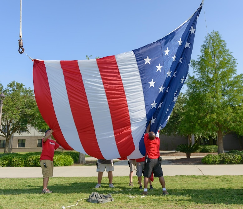 Keesler volunteers lift an U.S. flag during the Special Olympics Mississippi 2017 Summer Games opening ceremonies at the Levitow Training Support Facility drill pad May 19, 2017, on Keesler Air Force Base, Miss. Founded in 1968, Special Olympics hosts sporting events around the world for people of all ages with special needs to include more than 700 athletes from Mississippi. (U.S. Air Force photo by Andre' Askew)