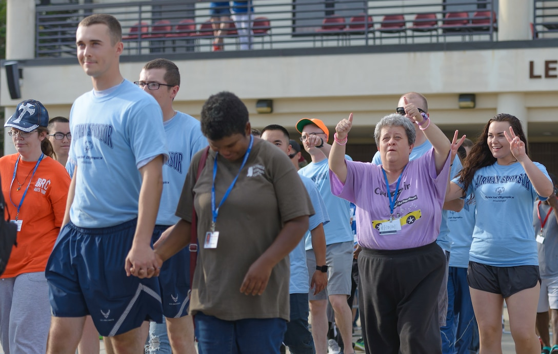 Airmen sponsors and athletes walk onto the Levitow Training Support Facility drill page during the Special Olympics Mississippi 2017 Summer Games opening ceremonies May 19, 2017, on Keesler Air Force Base, Miss. Founded in 1968, Special Olympics hosts sporting events around the world for people of all ages with special needs to include more than 700 athletes from Mississippi. (U.S. Air Force photo by Andre' Askew)