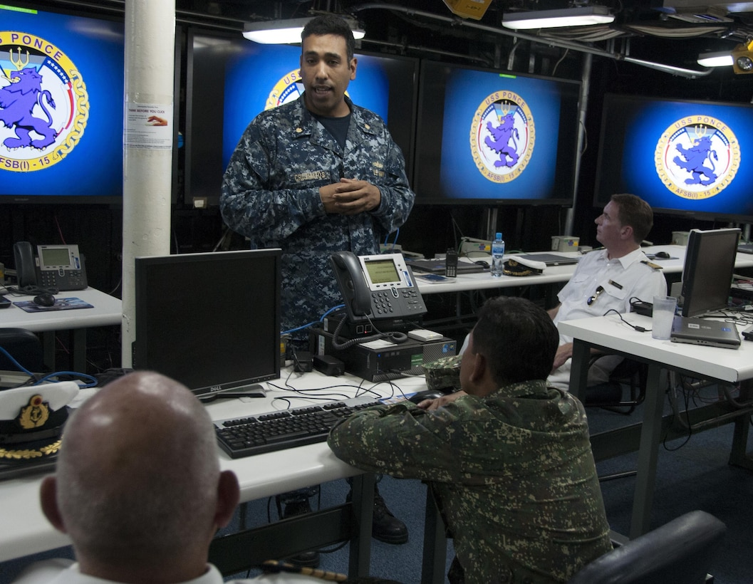 Lt. Cmdr. Edward Cruzmatos discusses the capabilities of Afloat Forward Staging Base (Interim) USS Ponce (AFSB(I)-15) with participants of the International Maritime Exercise (IMX) 2017. IMX is a command post exercise and includes more than 20 partner nations to promote interoperability, increase readiness in all facets of defensive maritime warfare and demonstrate resolve in maintaining regional security and stability and protecting the free flow of commerce. (U.S. Navy photo by Mass Communication Specialist 1st Class Grant P. Ammon)
