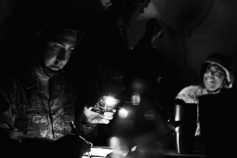 U.S. Air Force Staff Sgt. Matthew Range, 20th Civil Engineer Squadron electrical systems journeyman, uses his phone to shine light on paperwork following a simulated power outage during operational readiness exercise Weasel Victory 17-07 at Poinsett Electronic Combat Range near Wedgefield, S.C., May 16, 2017. Airmen were required to adapt to changing condition in order to complete the mission. (U.S. Air Force photo by Airman 1st Class Christopher Maldonado)