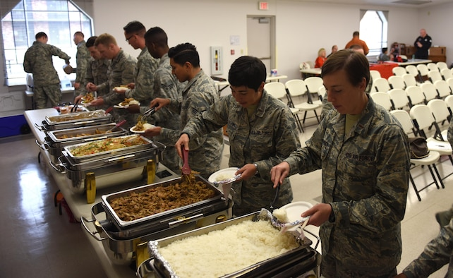 Airmen plate food at an Asian buffet at the beginning of the Asian-American and Pacific-Islander observation day at the Taylor Chapel on Goodfellow Air Force Base, Texas, May 23, 2017. Foods varied from different origin's styles such as Vietnamese, Japanese and Filipino. (U.S. Air Force photo by Airman 1st Class Caelynn Ferguson/Released)