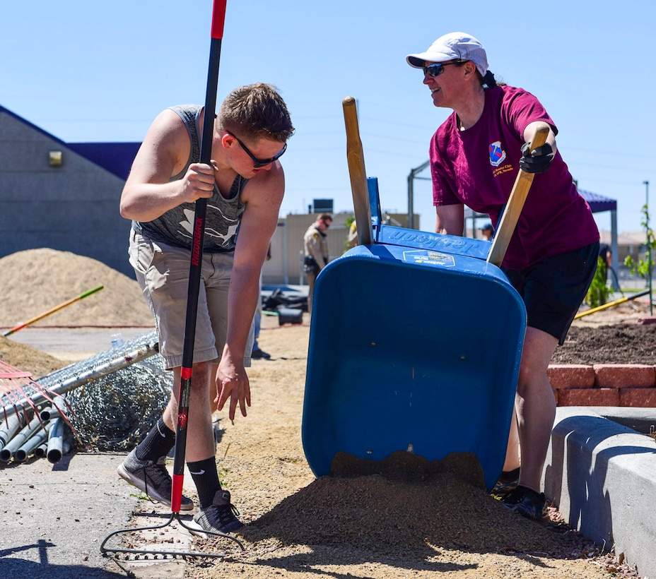 Col. Virginia Garner, 99th Medical Group commander, empties dirt from a wheelbarrow while Airman Logan Gaines, 99th Medical Group mental health technician, prepares to spread the dirt at a community garden between J.E. Manch and Zel & Mary elementary schools, May 12, 2017. Airmen from Nellis Air Force Base volunteered with community members to build a garden that will be used by the elementary schools for outdoor and environmental education. (U.S. Air Force photo by Airman 1st Class Andrew D. Sarver/Released)