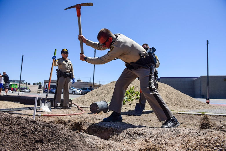 A Las Vegas Metro Police officer uses a pickaxe to loosen dirt at a community garden between J.E. Manch and Zel & Mary elementary schools, May 12, 2017. Members from the community, including Metro Police officers, local school teachers and Nellis Air Force Base Airmen, volunteered to plant trees, spread gravel and build benches and garden beds to create a garden for the elementary schools and neighborhood to use. (U.S. Air Force photo by Airman 1st Class Andrew D. Sarver/Released)