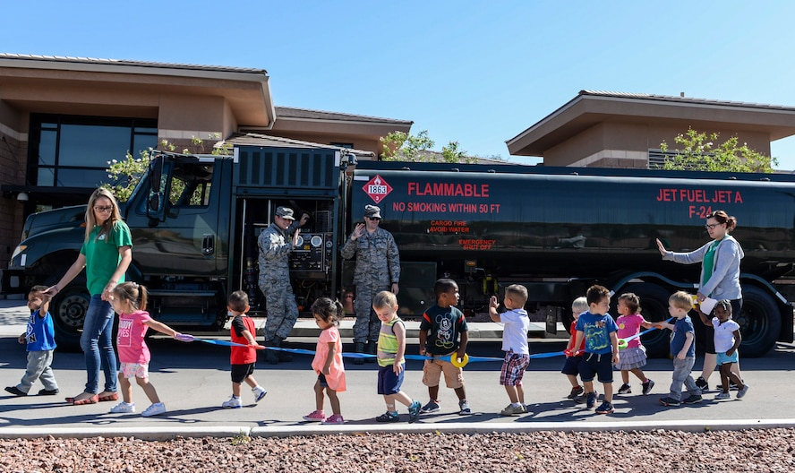 Children wave to Airmen assigned to the 99th Logistics Readiness Squadron standing in front of an R-11 Refueler truck at Nellis Air Force Base, Nev., May 16, 2017. The truck is capable of storing nearly 6,000 gallons of fuel. (U.S. Air Force photo by Airman 1st Class Andrew D. Sarver/Released)