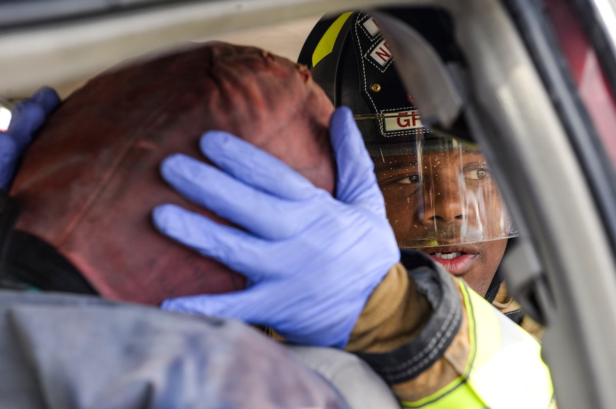 A firefighter from the 99th Civil Engineer Squadron stabilizes the head of a simulated car crash victim at Nellis Air Force Base, Nev., May 17, 2017. The simulation required vehicle operators from the 99th Logistics Readiness Squadron to flip an overturned vehicle. Firefighters then arrived on scene to evacuate the driver by cutting the roof off the crashed vehicle. (U.S. Air Force photo by Airman 1st Class Andrew D. Sarver/Released)