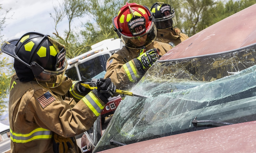 Firefighters from the 99th Civil Engineer Squadron remove a windshield during a simulated car crash at Nellis Air Force Base, Nev., May 17, 2017. The process of evacuating car crash victims includes removing the doors, cutting off the roof and raising the dashboard away from the front seats. (U.S. Air Force photo by Airman 1st Class Andrew D. Sarver/Released)