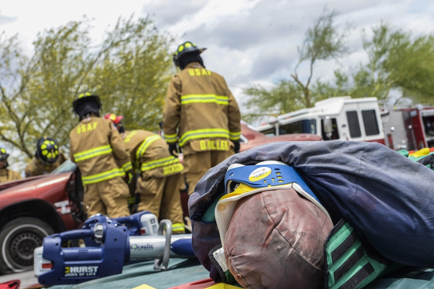 Firefighters from the 99th Civil Engineer Squadron prepare to lift the dashboard from the front seats of a simulated car crash at Nellis Air Force Base, Nev., May 17, 2017. The simulation required firefighters to respond to an overturned vehicle in which the victim had to be evacuated, by removing the doors and roof of the vehicle. (U.S. Air Force photo by Airman 1st Class Andrew D. Sarver/Released)