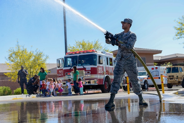 Airman 1st Class Michael Tuck, 99th Civil Engineer Squadron firefighter, shoots water out of a firehose at the child development center at Nellis Air Force Base, Nev., May 16, 2017. The display was part of the Touch-A-Truck event for National Defense Transportation Week. (U.S. Air Force photo by Airman 1st Class Andrew D. Sarver/Released)