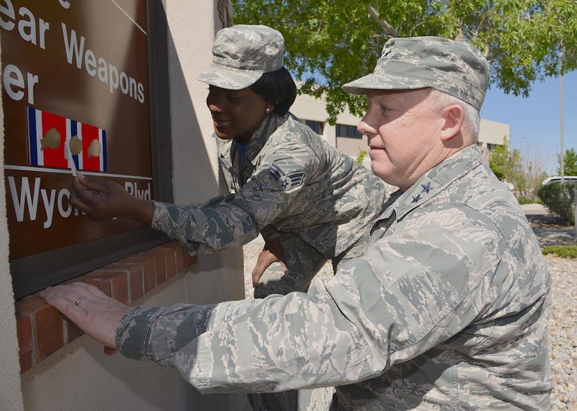 Maj. Gen. Scott W. Jansson, Air Force Nuclear Weapons Center commander and its most senior member, and Senior Airman Mychavia T. Harris, the center's most junior member in 2015, affix the third oak leaf cluster to the Air Force Organizational Excellence Award ribbon on the AFNWC headquarters' sign at Kirtland AFB, New Mexico.  The center was recognized for its 2015 achievements and accomplishments in nuclear materiel management in support of the nuclear deterrence mission.