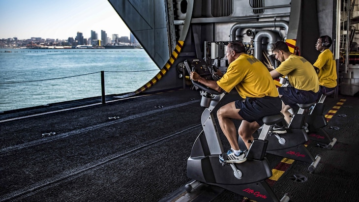 Sailors conduct their biannual physical readiness test on stationary bikes in the hangar bay of the aircraft carrier USS Theodore Roosevelt as the ship is moored pier-side in San Diego, May 22, 2017. Navy photo by Seaman Bill M. Sanders