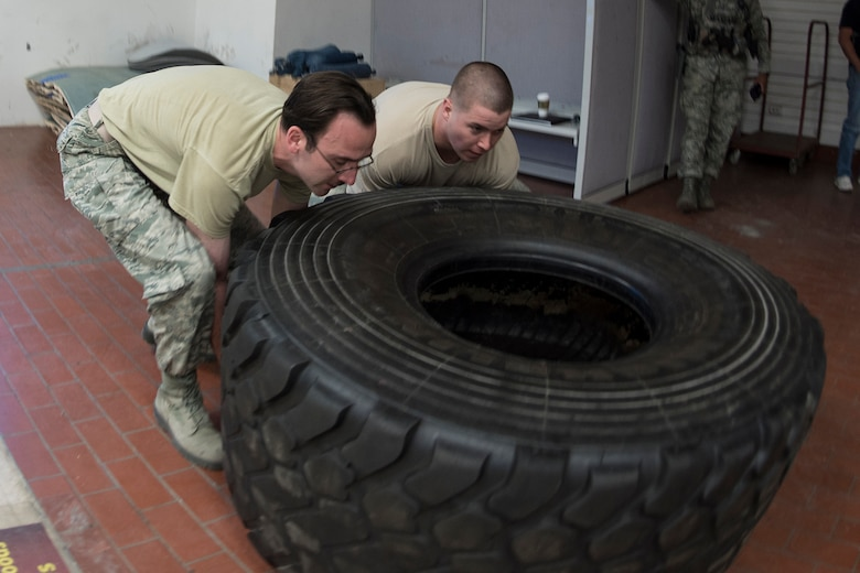 PETERSON AIR FORCE BASE, Colo. – Team Pete Airmen flip a tire during an obstacle course for National Police Week, May 18, 2017 at Peterson Air Force Base, Colo. The obstacle course was one of several events the 21st Security Forces Squadron hosted for Police Week, May 15-19, including a distracted driving simulator, combatives tournament, and BBQ. (U.S. Air Force photo by Steve Kotecki)