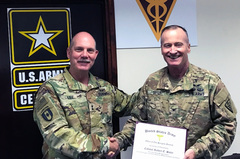 Maj. Gen. William Lee, commanding general, 3rd Medical Command (Deployment Support), presents the Maj. Gen. Lewis Aspey Mologne Award to Col. Robert E. Suter, commander, 3rd Medical Command (Deployment Support) Forward, at Camp As Sayliyah, Qatar, April 20, 2017. Suter was selected by the Office of the Surgeon General to receive the award. It is presented annually to one Active and one Reserve Medical Corps officer who the selection board feels best emulates Mologne by exhibiting a balance between outstanding leadership in military medicine and leadership in academics on a national level.