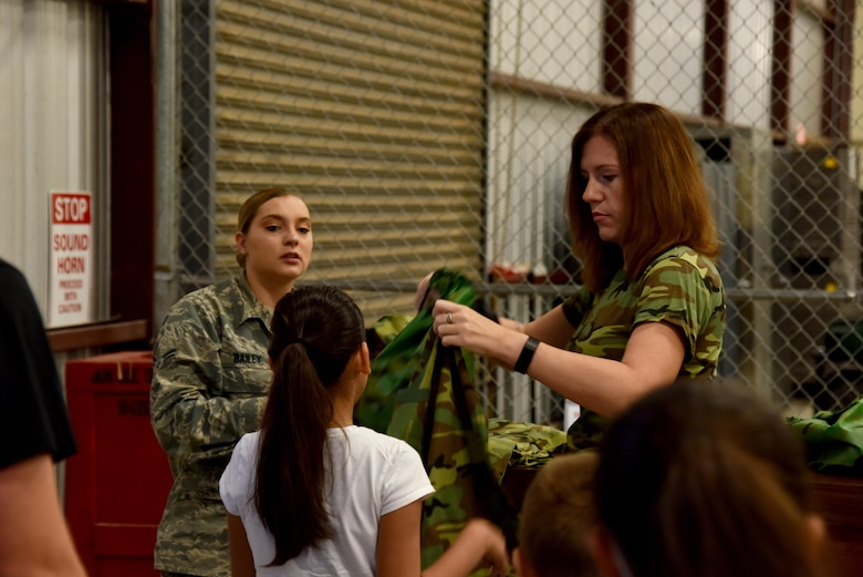 U.S. Air Force Staff Sgt. Jennifer Wagner, 17th Training Wing command chief executive assistant, and Airman 1st Class Caitlyn Bailey, 17th Logistic Readiness Squadron logistics planner, hand out deployment kits for Operation: Kids Investigating Deployed Services at the Vance Deployment Center on Goodfellow Air Force Base, Texas, May 20, 2017. Operation: K.I.D.S. exposed military and non-military children to a mock deployed experience. (U.S. Air Force photo by Staff Sgt. Joshua Edwards/Released)