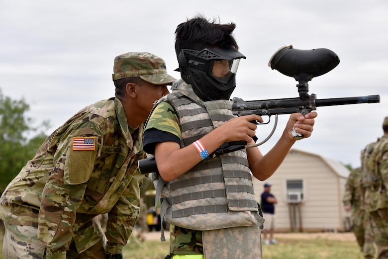 U.S. Army Pvt. Ricky Williams, 344th Military Intelligence Battalion student, teaches Dominick Cardens, Operation: Kids Investigating Deployed Services deployer, how to shoot a paintball gun during Operation: K.I.D.S. at Camp Sentinel on Goodfellow Air Force Base, Texas, May 20, 2017. Goodfellow's Army and Marine Corps help provide the children with a joint-service mock deployment for Operation K.I.D.S. (U.S. Air Force photo by Staff Sgt. Joshua Edwards/Released)