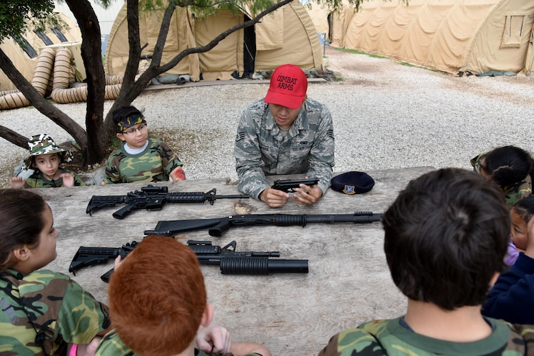 U.S. Air Force Staff Sgt. Nestor Reyes, 17th Security Force Squadron Combat Arms instructor, teaches children about Air Force issued weapons during Operation: Kids Investigating Deployed Services at Camp Sentinel on Goodfellow Air Force Base, Texas, May 20, 2017. The weapon familiarization and other activities gave the children a taste of a deployment. (U.S. Air Force photo by Staff Sgt. Joshua Edwards/Released)