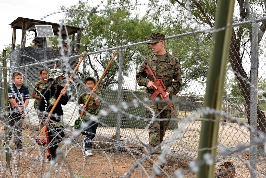 U.S. Marine Corps Lance Cpl. Noah Tait, Goodfellow Marine Corps Detachment student, starts a patrol with children during Operation: Kids Investigating Deployed Services at Camp Sentinel on Goodfellow Air Force Base, Texas, May 20, 2017. Each child had chance to understand what the armed services go through during a deployment. (U.S. Air Force photo by Staff Sgt. Joshua Edwards/Released)