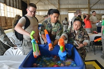 U.S. Airmen fill up water guns during the 2017 Combat Dining Out in Hangar 1200 at Shaw Air Force Base, S.C., May 19, 2017. During the event, Team Shaw members partook in water gun and water balloon fights. (U.S. Air Force photo by Airman 1st Class Destinee Sweeney)