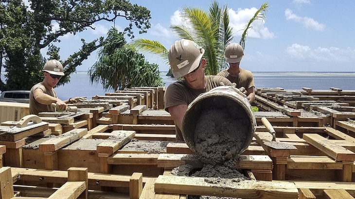 Navy Petty Officer 3rd Class Alexander Zebro pours cement for the bond beam of a health clinic that Naval Mobile Construction Battalion 1 is building in Kosrae, Micronesia, May 16, 2017. Navy photo by Petty Officer Matthew Konopka