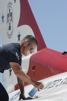 Staff Sgt. Jesse Barker, Thunderbird #1 crew chief, cleans his F-16 Fighting Falcon in preparation for a performance during Tinker Air Force Base's Star Spangled Salute air show May 20, 2017, Tinker Air Force Base, Oklahoma. Barker removed dirt and grime from the highly-polished jet with a wet rag. (U.S. Air Force photo/Greg L. Davis)