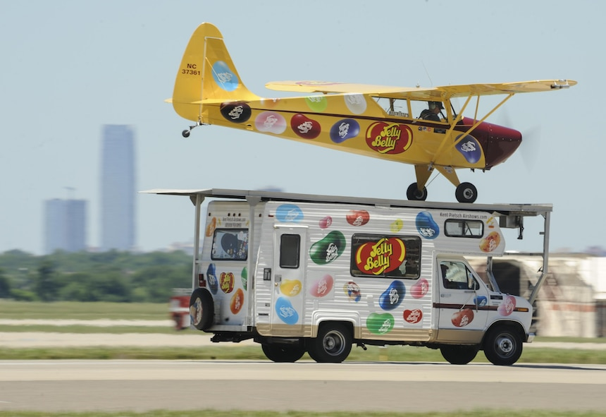 The Jelly Belly Interstate Cadet flown by Kent Pietsch lands on the roof of an RV barreling down the runway while the iconic skyline of Oklahoma City can be seen in the background during Tinker Air Force Base's Star Spangled Salute air show May 21, 2017, Tinker Air Force Base, Oklahoma. The air show had record attendance of over 100,000+ people due to clear skies, mild temperatures and a great line-up of military and civilian acts. (U.S. Air Force photo/Greg L. Davis)
