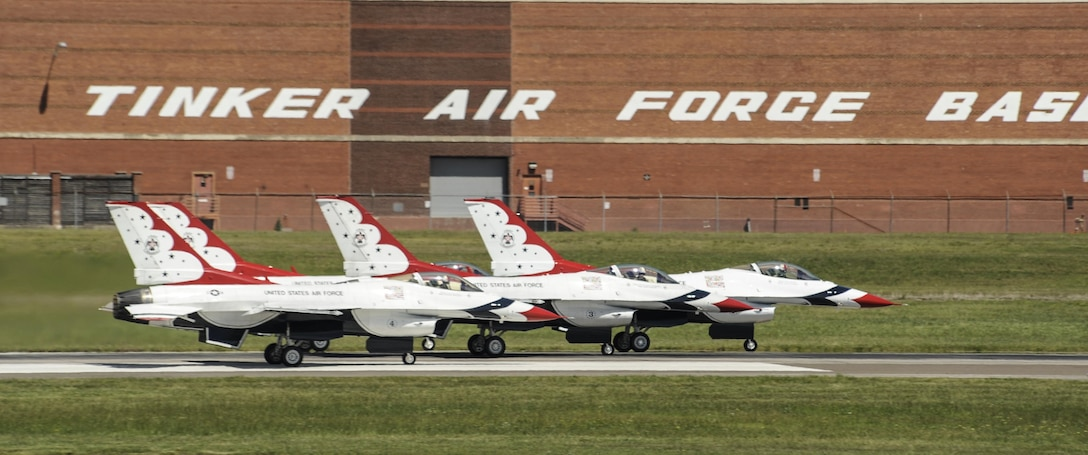 Four Thunderbird F-16s accelerate down the runway with the Tinker Air Force Base signage on building 3001 visible above them to begin their display during Tinker Air Force Base's Star Spangled Salute air show May 21, 2017, Tinker Air Force Base, Oklahoma. The Thunderbirds performed to record crowds during the weekend as the stars of the show. (U.S. Air Force photo/Greg L. Davis)