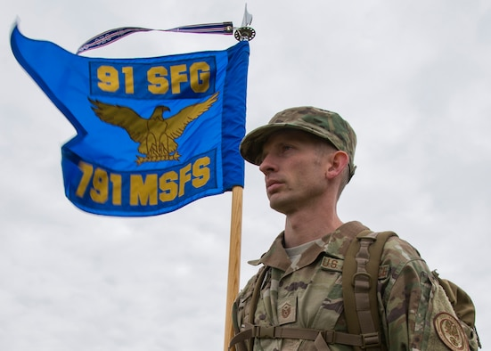 Master Sgt. Christopher Davis, 791st Missile Security Forces Squadron first sergeant, carries the guidon during the National Police Week 5K Remembrance Ruck March at Minot Air Force Base, N.D., May 16, 2017. During the week, Minot AFB security forces personnel planned a parade, weapon and vehicle display, 5K Remembrance Ruck March, 5K Memorial Run, and a retreat ceremony to end the week. (U.S. Air Force photo/Airman 1st Class Alyssa M. Akers)