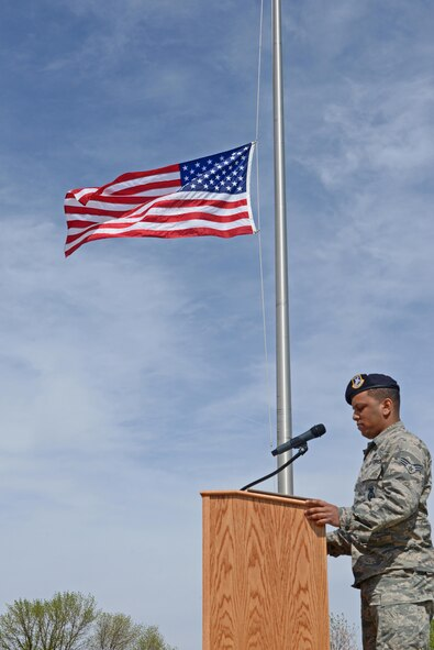 Senior Airman Eduardo Virgil, 5th Security Forces Squadron desk sergeant, recites fallen officers' names during a National Police Week retreat ceremony at Minot Air Force Base, N.D., May 19, 2017. A retreat ceremony is the daily military practice of lowering the flag. (U.S. Air Force photo/Airman 1st Class Austin M. Thomas)