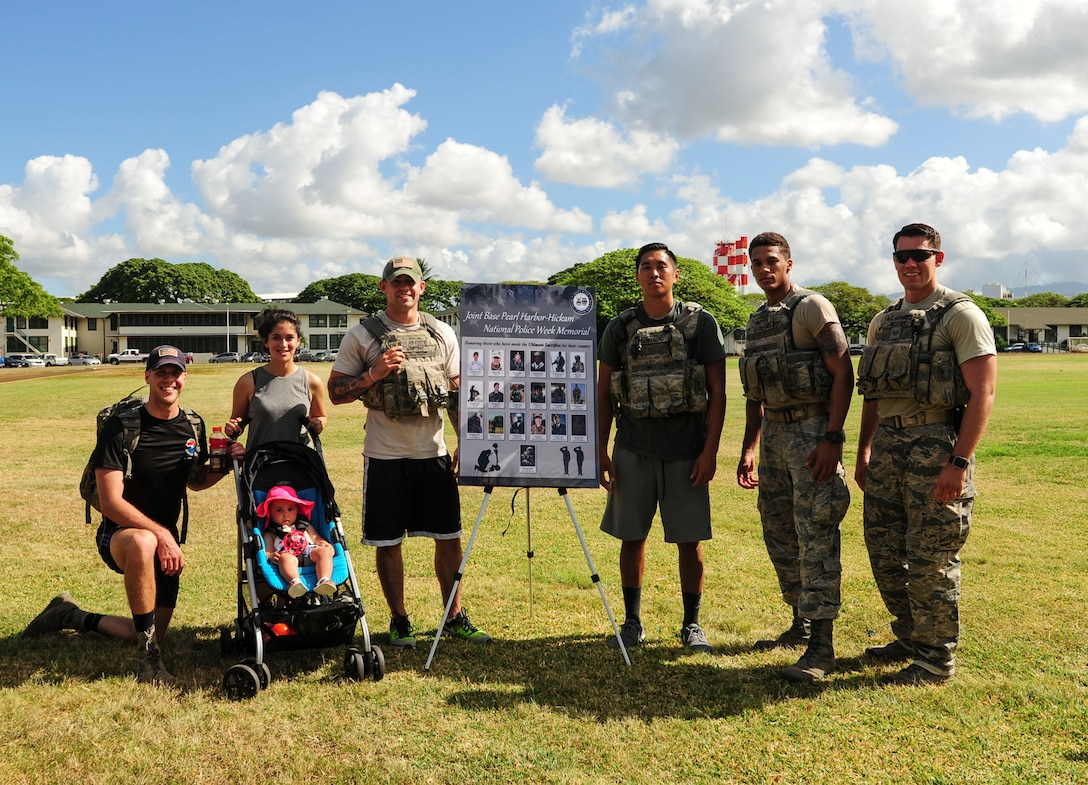 Joint Base Security Forces (JBSF) Airmen pose for a group photo at the end of the Police Week Ruck March, on Joint Base Pearl Harbor-Hickam, Hawaii, May 19, 2019. According to the National Peace Officer's Memorial Fund website, National Police Week was established in 1962 by President John F. Kennedy to pay tribute to law enforcement officers who lost their lives in the line of duty. Ceremonies and observances are held annually throughout the U.S. in remembrance of fallen officers.  (U.S. Air Force photo by Tech. Sgt. Heather Redman)