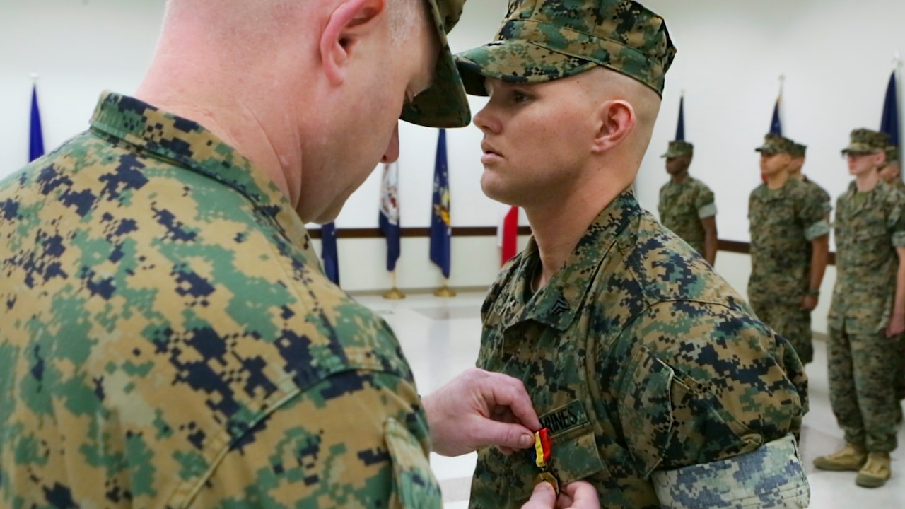 Lt. Col. Vincent Dawson (left), the executive officer of Marine Aircraft Group 41, Marine Forces Reserve, awards Cpl. David Qualls, a motor transport assistant operations chief with Marine Wing Support Squadron 471, 4th Marine Aircraft Wing, MARFORRES, the Navy and Marine Corps medal at the 1st Battalion, 23rd Marine Regiment headquarters in Houston, Texas, May 20, 2017. In 2014, Qualls helped save a man stuck in a burning vehicle. According to Qualls' award summary, had he not arrived when he did, the man would have surely died. (U.S. Marine Corps photo by Cpl. Dallas Johnson)