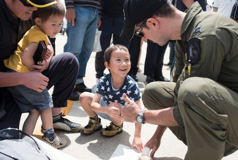 U.S. Air Force Capt. Dakota Newton, a Pacific Air Forces F-16 Demonstration Team safety observer, shares a thumbs up with a young boy during the Hofu Air Festival at Hofu-kita Air Base, Japan, May 21, 2017. The interaction with community is one aspect of the teams overall mission, the other being a display of the F-16 Fighting Falcons air power. (U.S. Air Force photo by Staff Sgt. Melanie Hutto)