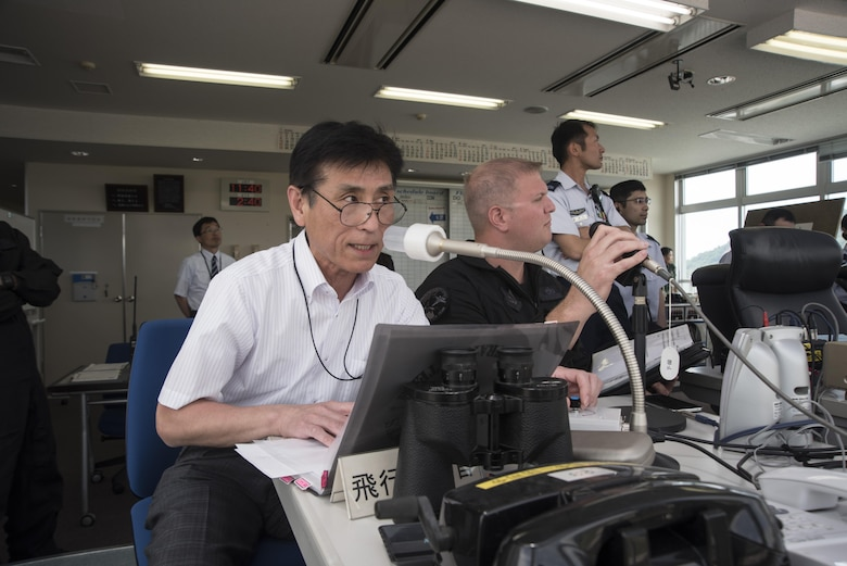 Hiromichi Nara, left, the Pacific Air Forces F-16 Demonstration Team translator and liaison, and U.S. Air Force Tech. Sgt. Tristan Berger, the PACAF F-16 Demonstration Team aerospace propulsion craftsman and narrator, announce the different maneuvers the demo pilot performs  during the Hofu Air Festival, May 21, 2017 at Hofu-kita Air Base, Japan. Nara joined the demo team at its inception almost 20 years ago. Berger became a team member one year ago. The primary objective of the team is to showcase the F-16 Fighting Falcon's capabilities to countries that fall within PACAF's area of responsibility. (U.S. Air Force photo by Staff Sgt. Melanie Hutto)