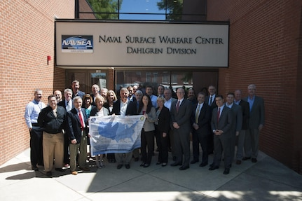 DAHLGREN, Va. - The Naval Laboratory Centers Coordinating Group (NLCCG) gathers outside of the Naval Surface Warfare Center Dahlgren Division (NSWCDD) headquarters as several members hold a poster depicting the Naval Research and Development Establishment commands and organizations.