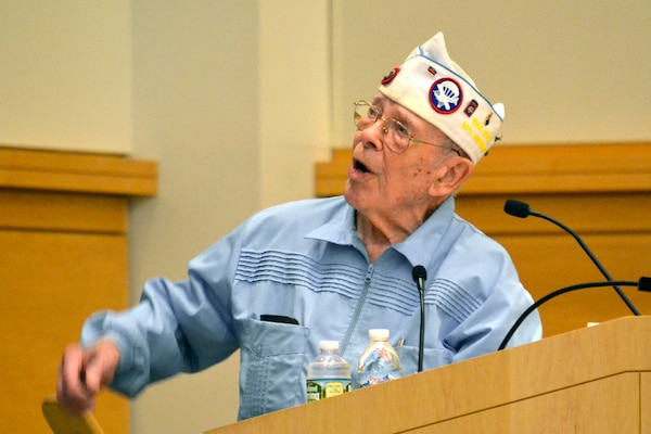 Les Cruise, a World War II veteran, relates stories of his experiences in Europe as a paratrooper with the 82nd Airborne Division, including the painful losses of his friends during combat, to the Naval Support Activity Philadelphia workforce during a Memorial Day observance May 18.