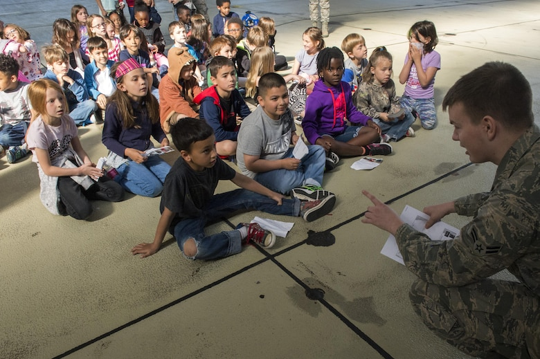 U.S. Air Force Airman 1st Class Kyle Hamby, 52nd Operations Support Squadron intelligence analyst, speaks to Spangdahlem Elementary School students during Children's Deployment Days at Spangdahlem Air Base, Germany, May 22, 2017. The event was a three-day simulated deployment line for students in kindergarten through fifth grade and consisted of a mock pre-deployment brief, a look at individual protective equipment, mock immunizations, static vehicle displays and a tour of a C-17 Globemaster III aircraft. (U.S. Air Force photo by Airman 1st Class Preston Cherry)
