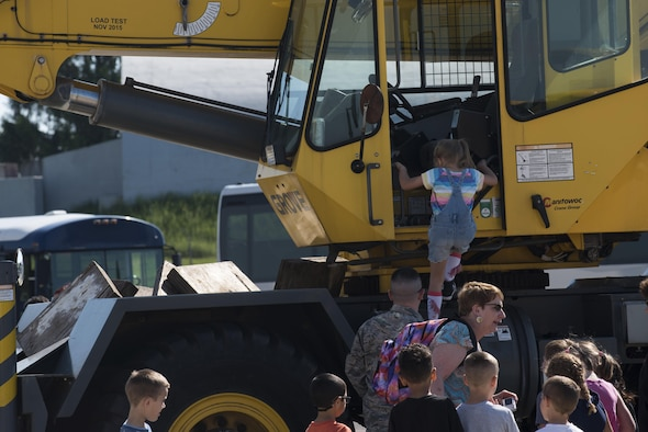 A Spangdahlem Elementary School student climbs into a 52nd Civil Engineer Squadron construction vehicle during Children's Deployment Days at Spangdahlem Air Base, Germany, May 22, 2017. The event taught children the process of how their parents prepare to deploy for real-world operations. (U.S. Air Force photo by Airman 1st Class Preston Cherry)