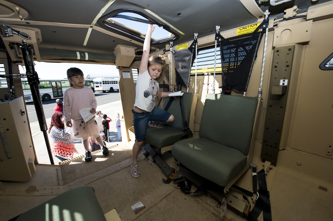Students from Spangdahlem Elementary School explore an armored vehicle during Children's Deployment Days at Spangdahlem Air Base, Germany, May 22, 2017. The deployment line featured several sections to inform children about deploying, including a pre-deployment brief, a look at deployment gear, mock immunizations, static vehicle displays and a tour of a C-17 Globemaster III aircraft. (U.S. Air Force photo by Airman 1st Class Preston Cherry)