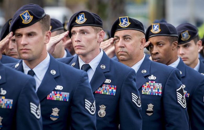 A formation of security forces Airmen salute during the posting of the colors at the Police Officers' Memorial Ceremony, May 18, 2017, in Fort Walton Beach, Fla. The ceremony was held to honor fallen police officers from the previous year by reading their names aloud. Security forces Airmen from Eglin Air Force Base and Hurlburt Field attended and participated in the event. The ceremony is one of many events taking place during National Police Week. (U.S. Air Force photo/Samuel King Jr.)