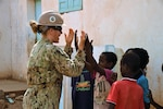 U.S. Navy Petty Officer 3rd Class Lacy P'Pool, Naval Mobile Construction Battalion ONE member of Combined Joint Task Force-Horn of Africa, plays a hand-clapping game with a student while on break near the Seabees job site in the Arta Region, Djibouti, May 18, 2017. The nearly 10-person team is working to build both a medical clinic and bond with the regional people. (Photo by U.S. Air National Guard photo by Tech. Sgt. Andria Allmond)