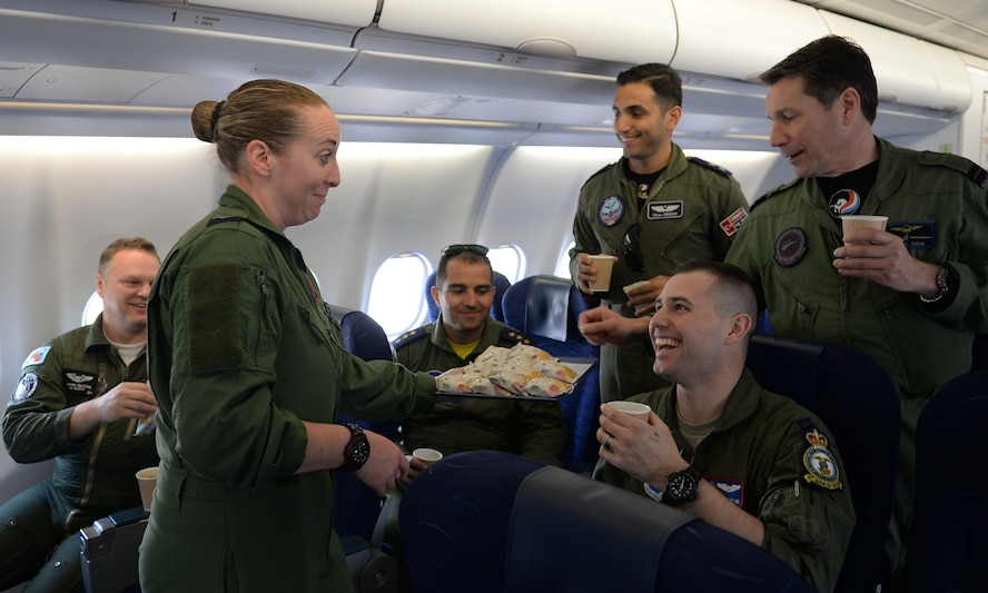 Royal Air Force Cpl. Niki Hargreaves, 10th Squadron cabin supervisor, serves snacks and drinks to the visiting crew on the Royal Air Force A330 Voyager during the European Tanker Symposium May 11, 2017, over England.  Pilots from different NATO countries went on board the Voyager to observe the mixed tanker formation. This was the first time two tankers from different countries took off from the same base in a mixed formation. (U.S. Air Force photo by Airman 1st Class Luke Milano)